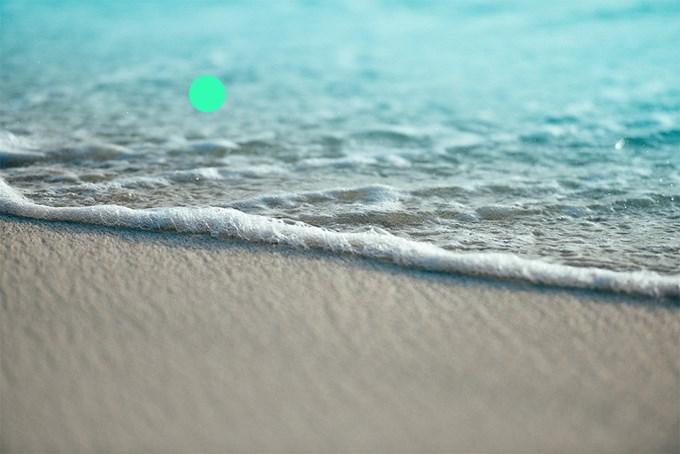Foto. Vann som skyller opp på stranden.