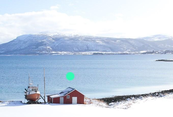 Foto. Båt står på land ved havet i norsk vinterlandskap.