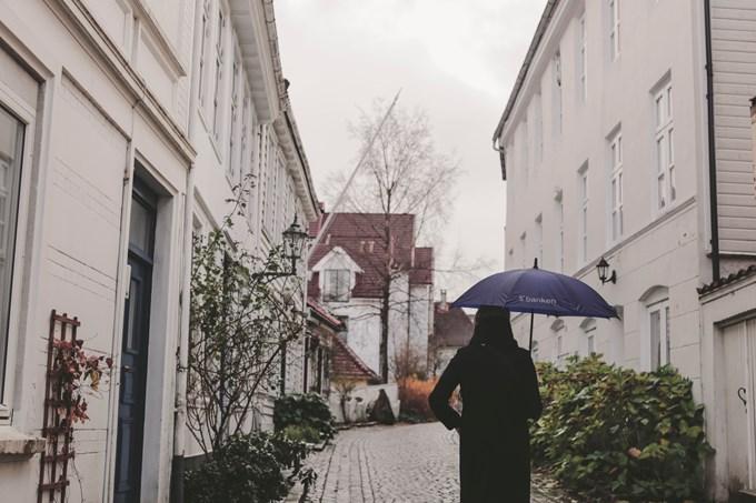Dame går i gate med paraply. Bilde