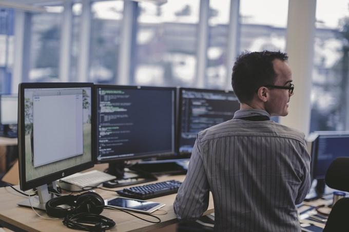 Bilde av utvikler som sitter ved arbeidsplassen sin i kontorlandskap.