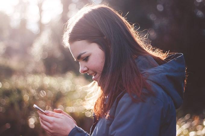 Ung kvinne ser på mobiltelefon.