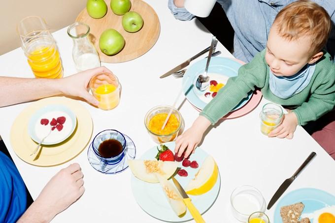 Frokostbord med frukt og familie. Foto