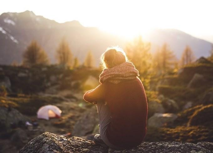 Bilde av person som sitter alene i naturen og ser på soldnedgangen.