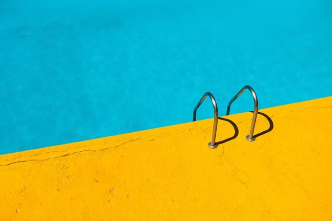 Bilde av svømmebasseng med blått vann og gul bassengkant.