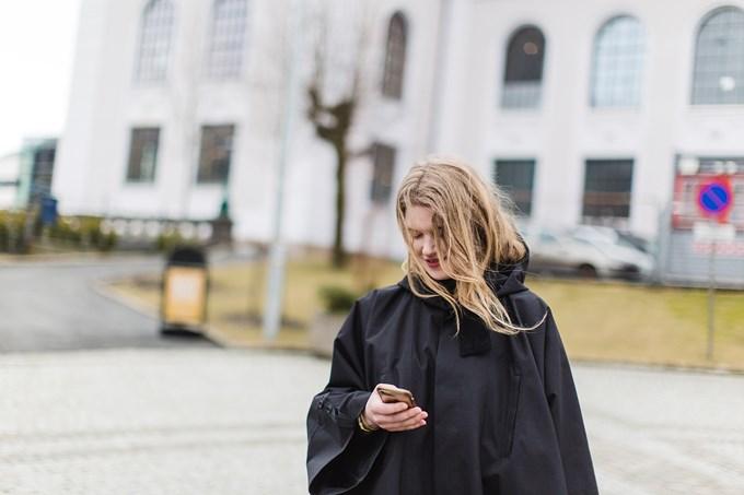 Bilde av ung kvinne i regnponcho som ser ned på en mobil i hånden.