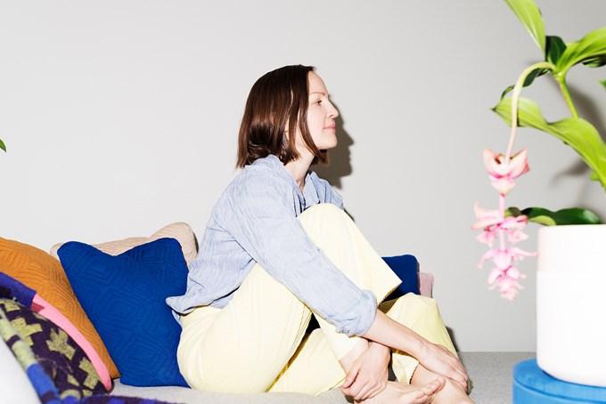 Dame sitter i sofa i bakkant av en grønn plante.