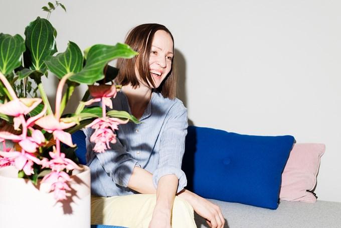 Foto. Dame sitter i sofa med grønn plante i forkant.