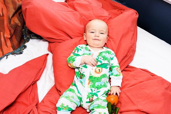 Foto baby ligger i sengen og smiler