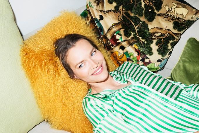 Dame med stripete bluse ligger på gul sofapute | foto