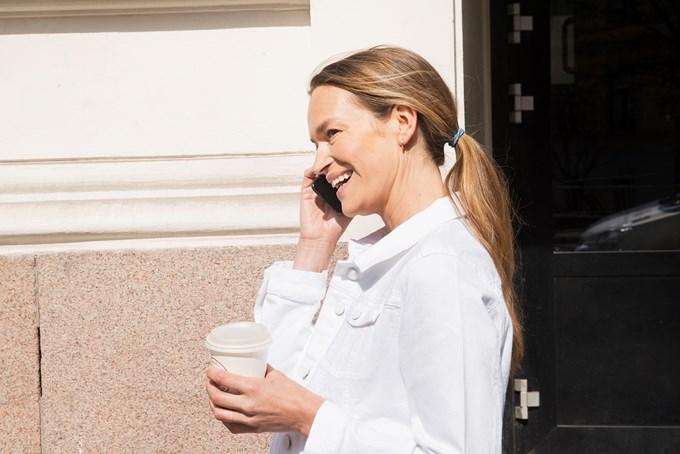 Dame går med kaffekopp i hånden mens hun snakker i telefonen. Bilde
