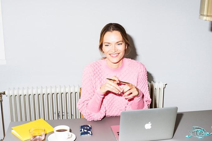 Foto av en dame som sitter ved arbeidsbordet og smiler