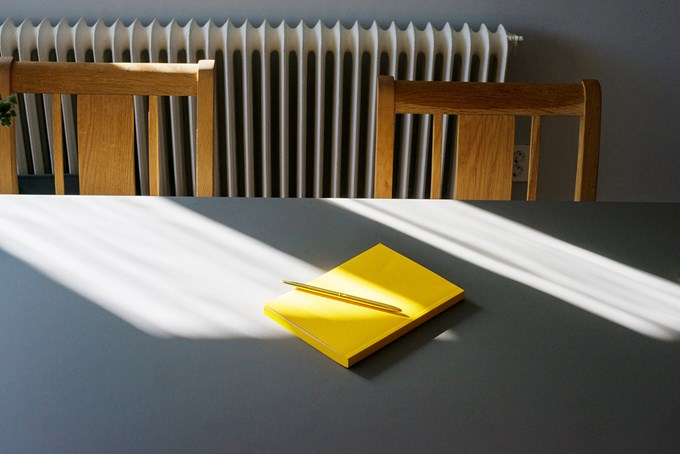 Gul notatblokk med penn opp liggende på bord med to stoler foto