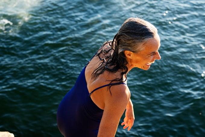 Foto av glad dame i blå badedrakt ved sjøen