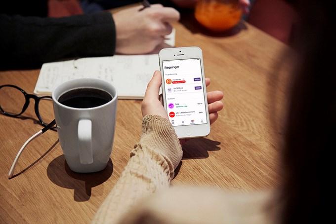 Vipps regninger_dame holder mobil som viser vipps regninger
