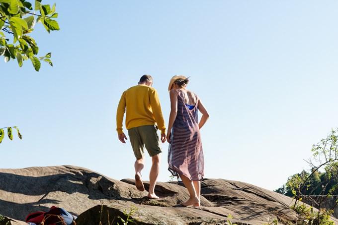 Mann og dame går på svaberg i sol | foto