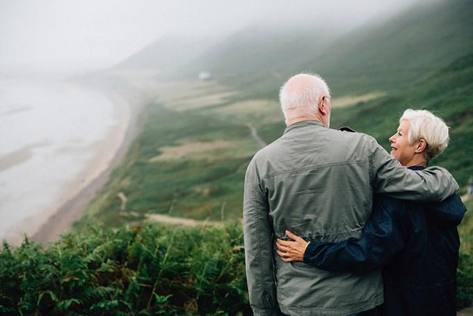 Mann og dame ser utover skog og strand
