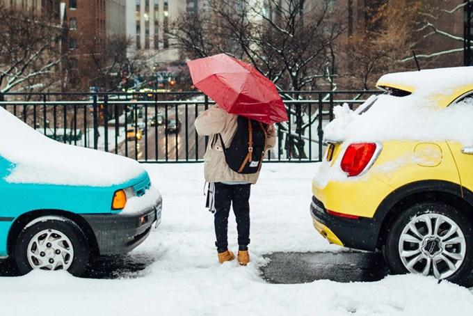 Foto av person som står med paraply mellom to biler