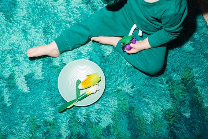 Foto barn med leker som sitter på et grønt teppe