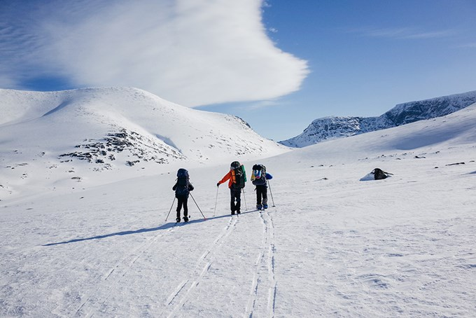 Foto av tre skigåere