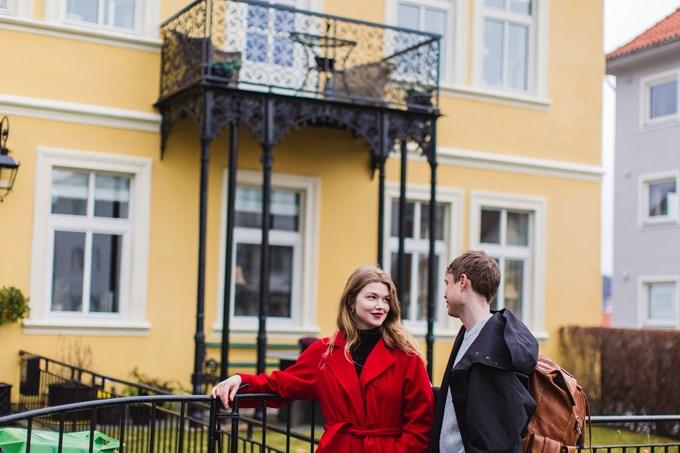 Foto av to personer foran et hus