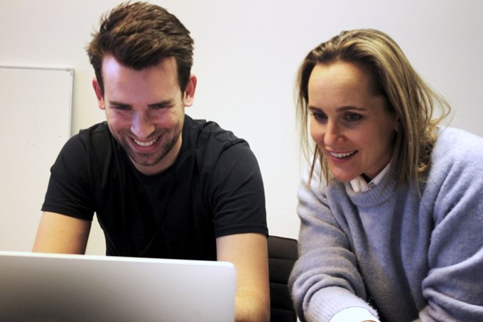 To Sbanken-ansatte ser på en pc-skjerm.