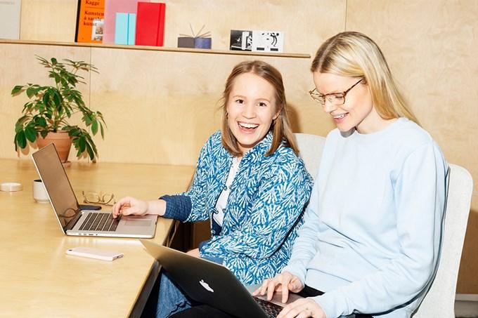 Foto av to kvinner som sitter ved datamaskinene og smiler