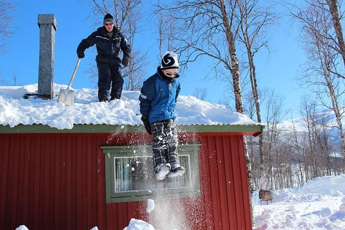 Gutt hopper i snøen. Bilde