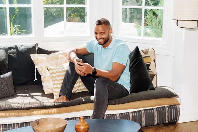 Foto av mann i sofa som smiler og ser på mobilen