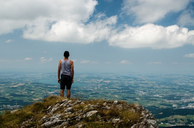 Mann med ryggen til ser utover landskap | foto