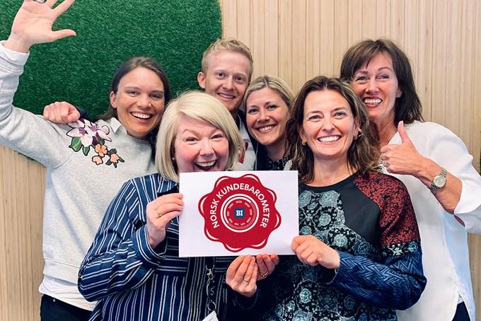 Glade ansatte holder ark med logoen til Norsk Kundebarometer | foto