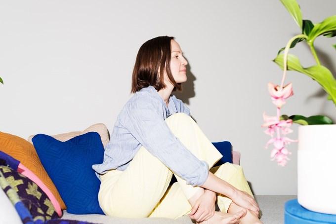 Dame som sitter i sofa, sees i profil, hun holder armene rundt det ene beinet sitt.