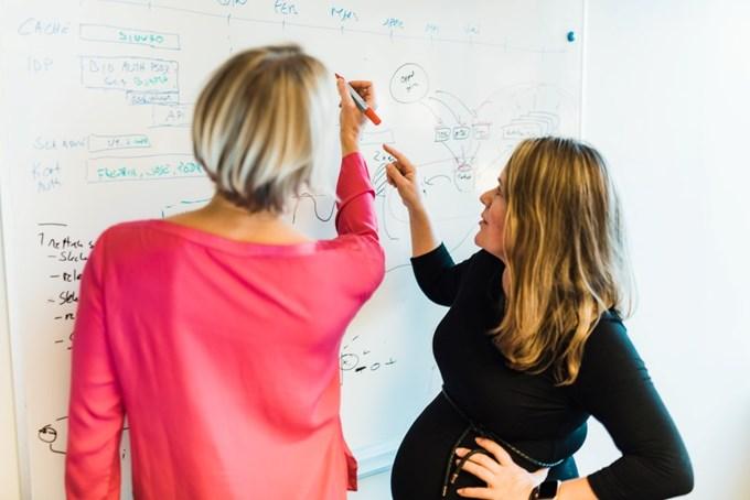 To damer står og skriver og ser på tavle