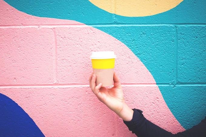 Hånd som holder kaffekopp foran fargerik vegg