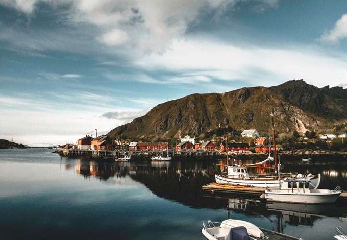 Bilde av fjell og fjord med båter.