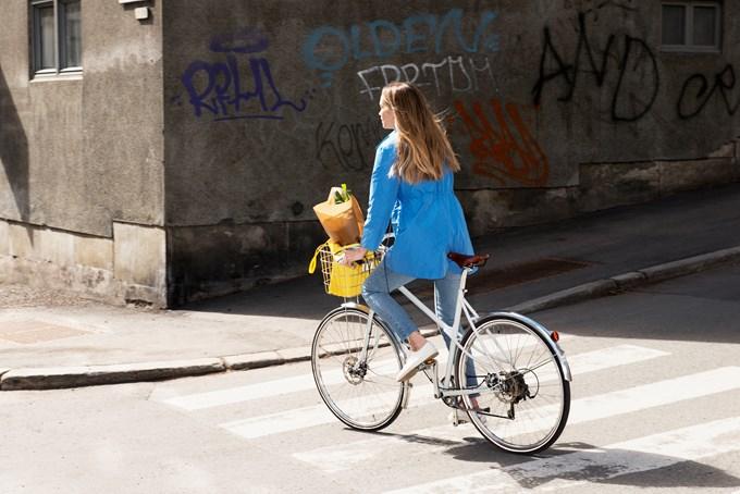 Foto av kvinne på sykkel sykler over fotgjengerfelt.