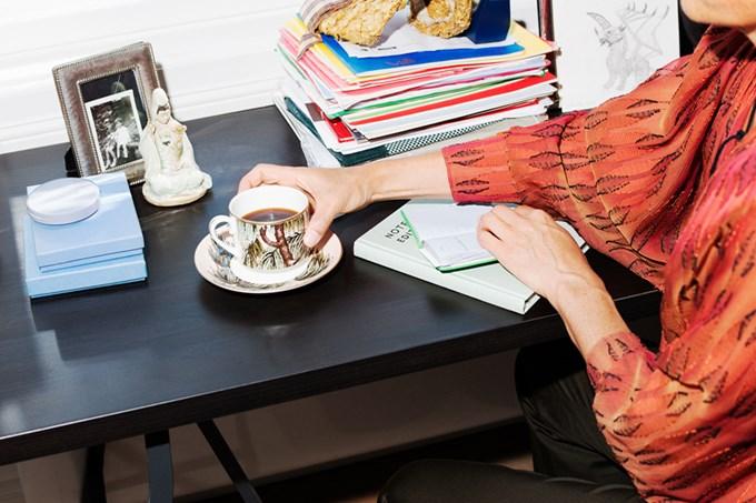 Dame i oransje kjole sitter ved bord og holder på en kaffekopp | foto