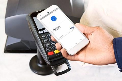 Hånd holder mobiltelefon mot betalingsterminal med godkjent Google Pay-betaling og Sbanken-kort | foto