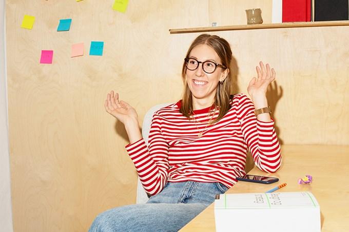 Bilde av dame som sitter ved et arbeidsbord.
