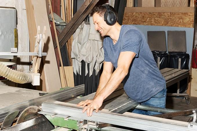 Smilende mann kapper en stålbjelke på verkstedet sitt.