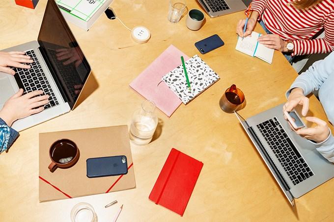 Tre kvinner med datamaskiner sitter på kontoret og jobber.