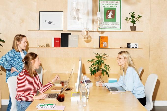Tre kollegaer diskuterer over arbeidsbordet foran datamaskinene sine.