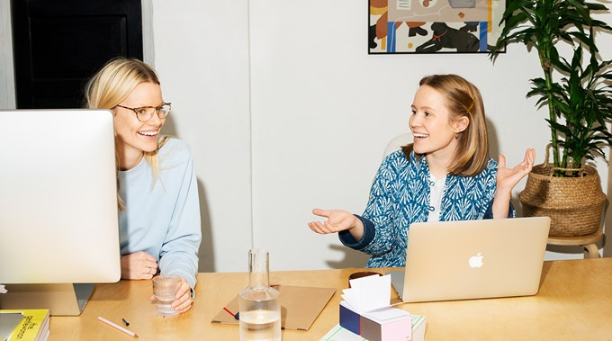 Bilde av to bedriftseiere som diskuterer på kontoret sitt.