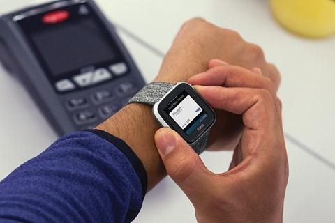 Mann som betaler med Fitbit-klokke, betalingsterminal i bakgrunnen | foto