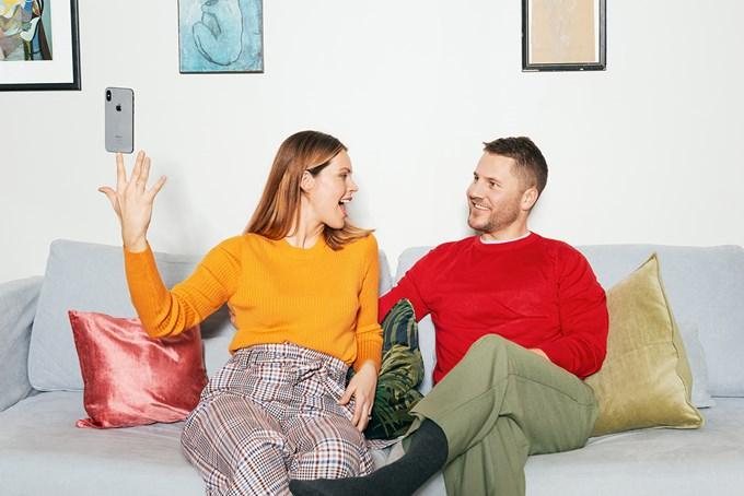 Mann og dame sitter i sofa, dame balanserer mobil på fingertuppen | foto