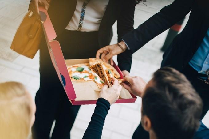 Bilde av personer som deler en pizza.