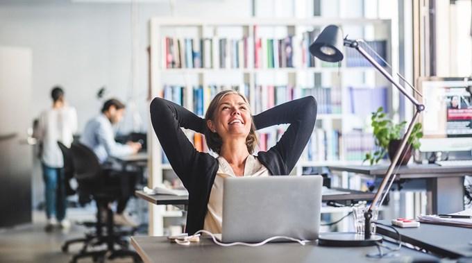 Bilde av dame som sitter ved kontorpult