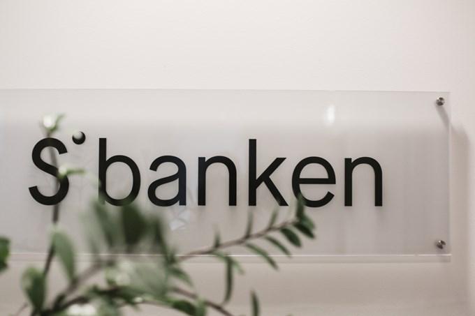 Sbankens logo på et skilt med grønn plante foran. Foto.