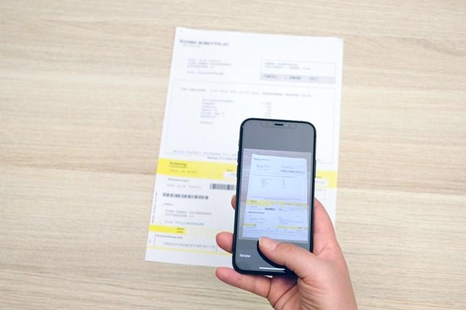 Hånd holder mobil, tar bilde av regning med fakturaskanner | foto