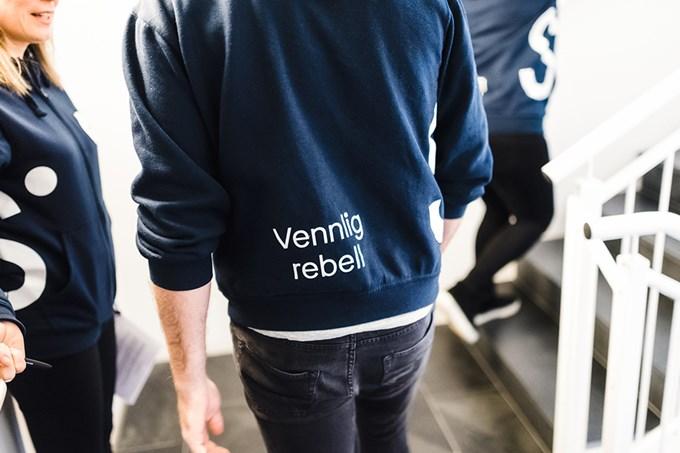 Ansatt med ryggen til og teksten Vennlig rebell på blå hettegenser   foto