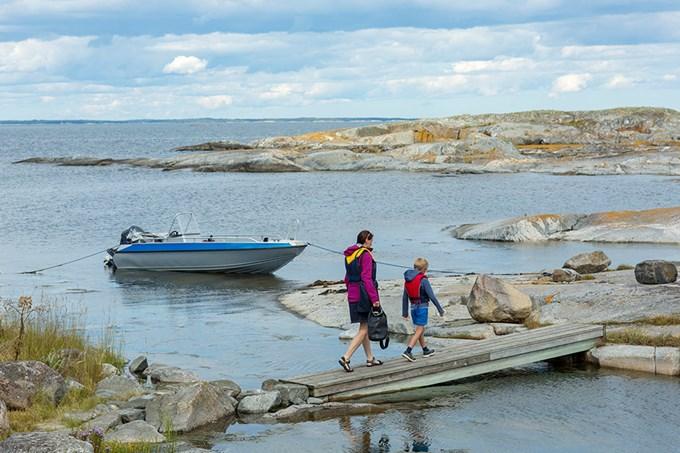 To personer går ut til båt som ligger fortøyd ved land. Foto.